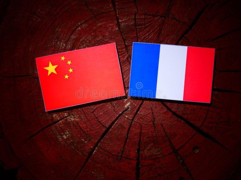 Drapeau chinois avec le drapeau français sur un tronçon d'arbre d'isolement images libres de droits