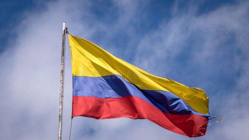 Drapeau colombien de ondulation sur un ciel bleu - Bogota, Colombie image stock