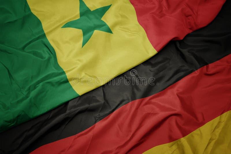 drapeau coloré de l' allemagne et drapeau national du sénégal photo stock