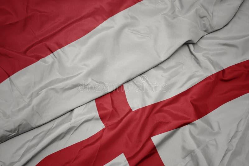 drapeau coloré de l' angleterre et drapeau national de l' indonésie photos stock