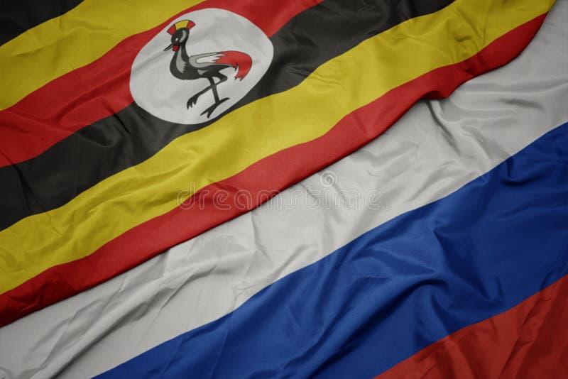 drapeau coloré de la russie et drapeau national de l' ouganda photos stock