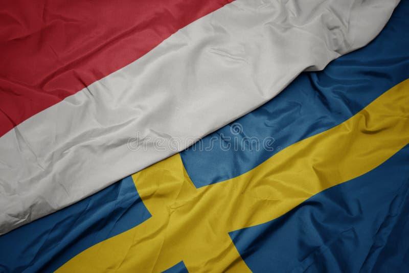 drapeau coloré de la suède et drapeau national de l' indonésie photos libres de droits