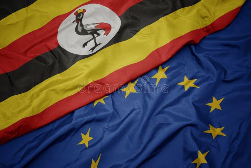 drapeau coloré de ondulation d'Union européenne et drapeau de l'Ouganda photographie stock
