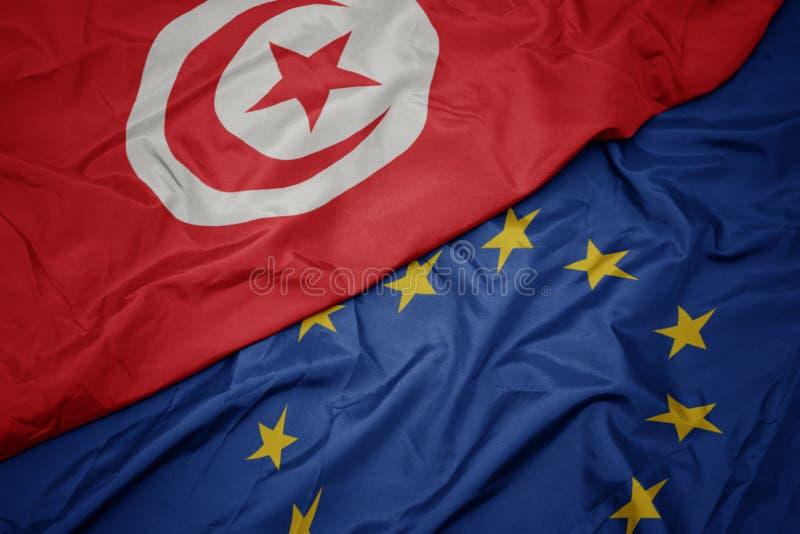 drapeau coloré de ondulation d'Union européenne et drapeau de la Tunisie photo libre de droits