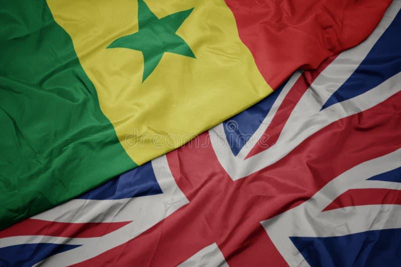 drapeau coloré de ondulation de la Grande-Bretagne et drapeau national du Sénégal photographie stock