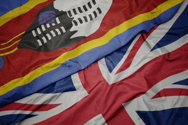 drapeau coloré de ondulation de la Grande-Bretagne et drapeau national du Souaziland photos libres de droits