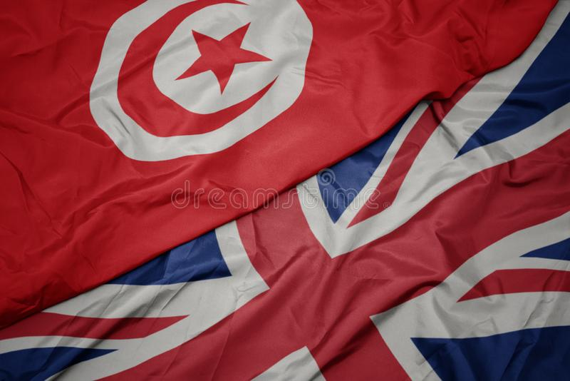 drapeau coloré de ondulation de la Grande-Bretagne et drapeau national de la Tunisie image stock