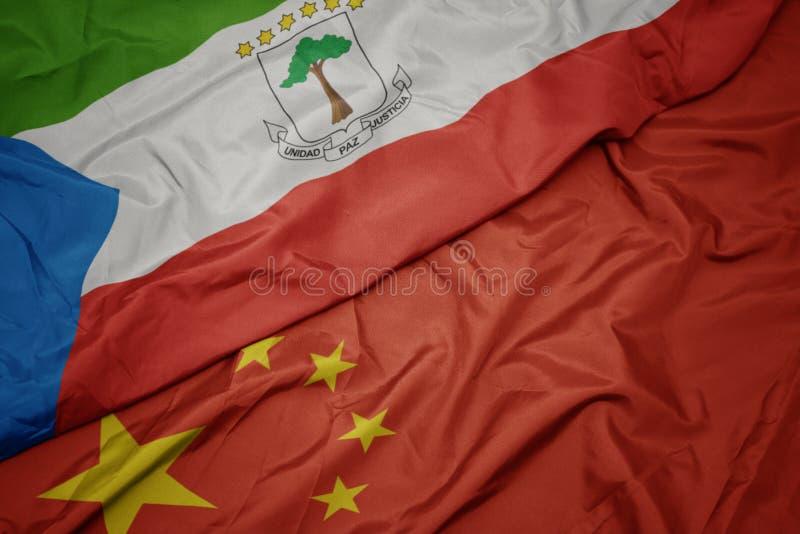 drapeau coloré de ondulation de porcelaine et drapeau national de Guinée équatoriale image libre de droits