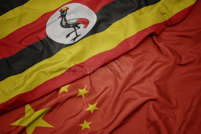 drapeau coloré de ondulation de porcelaine et drapeau national de l'Ouganda photo stock