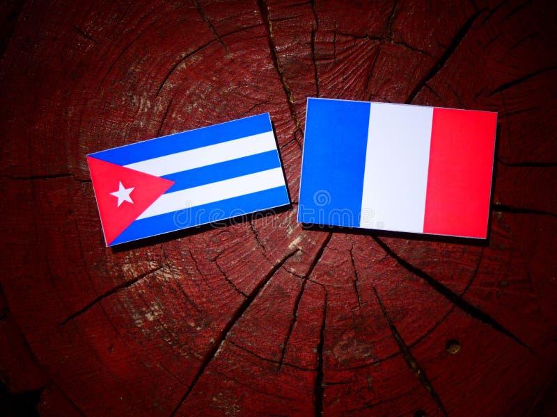 Drapeau cubain avec le drapeau français sur un tronçon d'arbre d'isolement image stock