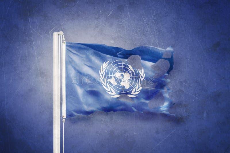 Drapeau déchiré des Nations Unies ondulant sur le fond grunge image stock