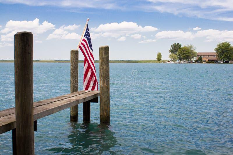 Drapeau d'Americain sur une carcasse avec le ciel bleu et le lac photographie stock