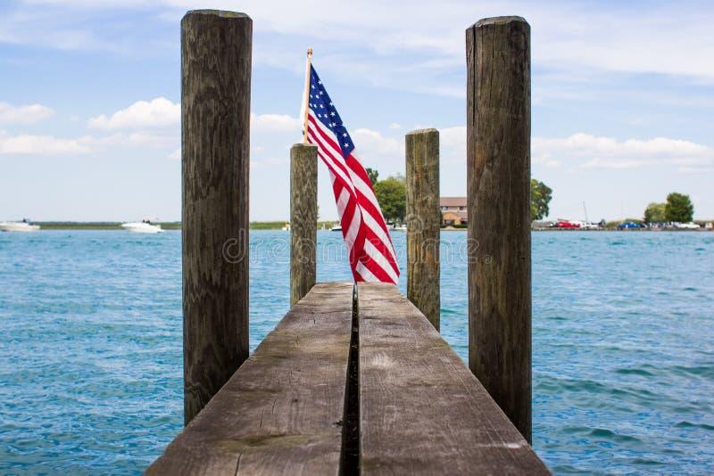 Drapeau d'Americain sur une carcasse avec le ciel bleu et le lac photo stock