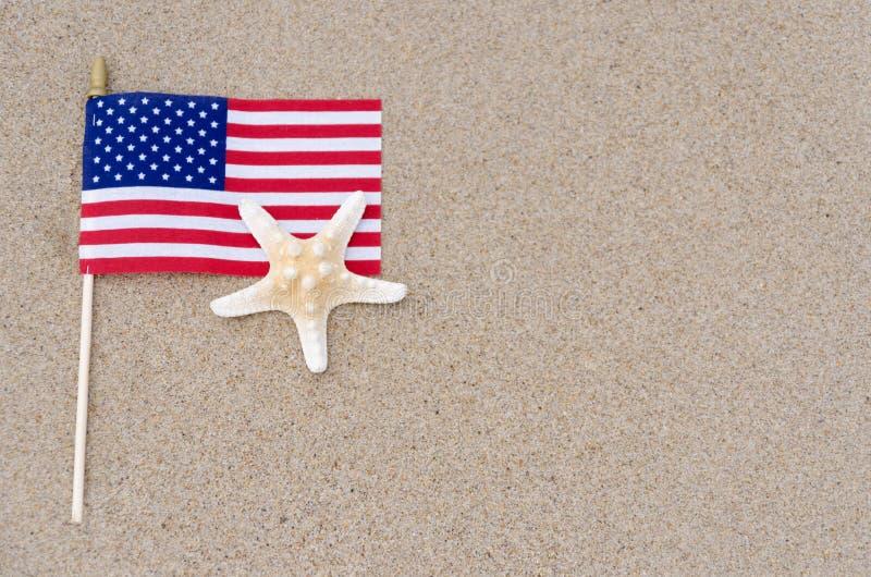Drapeau d'Amrican avec des étoiles de mer sur la plage sablonneuse images stock