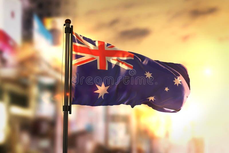 Drapeau d'Australie sur le fond brouillé par ville au lever de soleil Backli photos stock