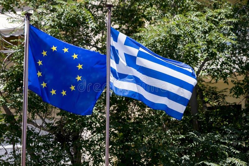 Drapeau d'Union européenne et drapeau grec, ondulant dans le vent photographie stock libre de droits
