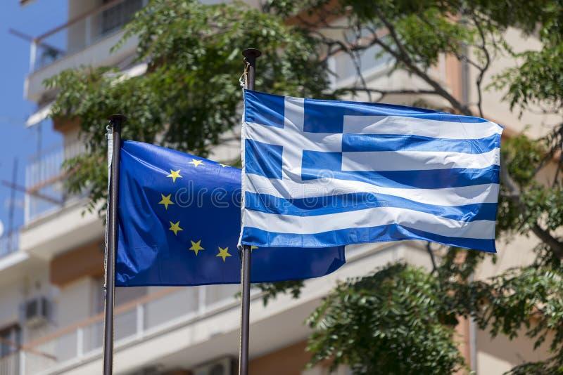 Drapeau d'Union européenne et drapeau grec, ondulant dans le vent photos stock