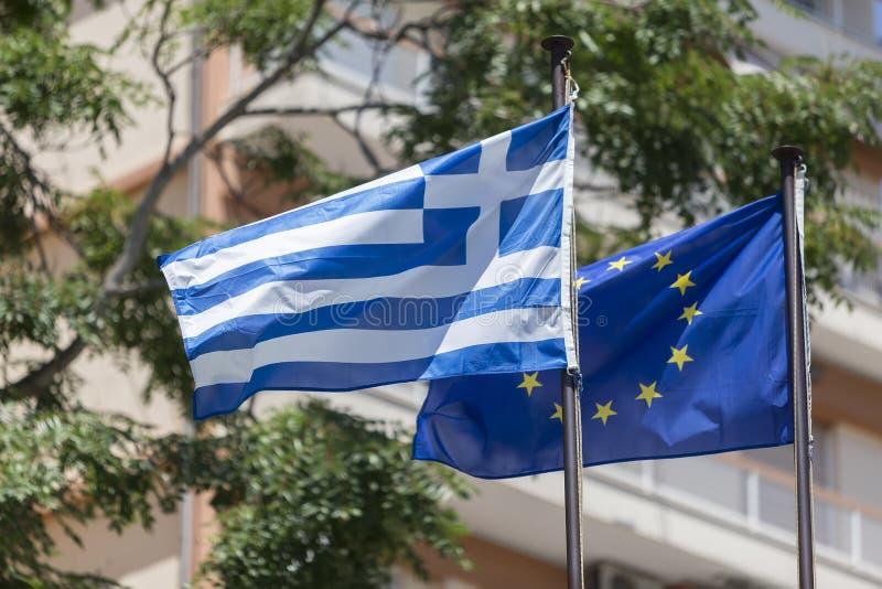 Drapeau d'Union européenne et drapeau grec, ondulant dans le vent photos libres de droits