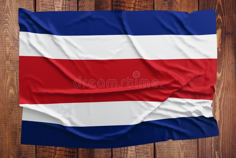 Drapeau de Costa Rica sur un fond en bois de table Vue sup?rieure froiss?e de drapeau de Costa Rican photo libre de droits