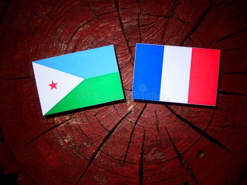 Drapeau de Djibouti avec le drapeau français sur un tronçon d'arbre d'isolement photo stock