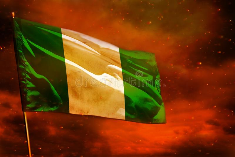 Drapeau de flottement du Nigéria sur le ciel rouge cramoisi avec le fond de piliers de fumée Préoccupe le concept photo libre de droits