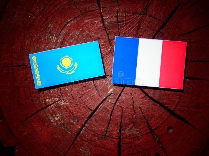 Drapeau de Kazakhstan avec le drapeau français sur un tronçon d'arbre d'isolement photo stock