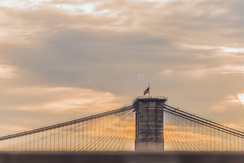 Drapeau de l'Amérique avec le ciel orange sur le pont de Brooklyn New York City photo stock