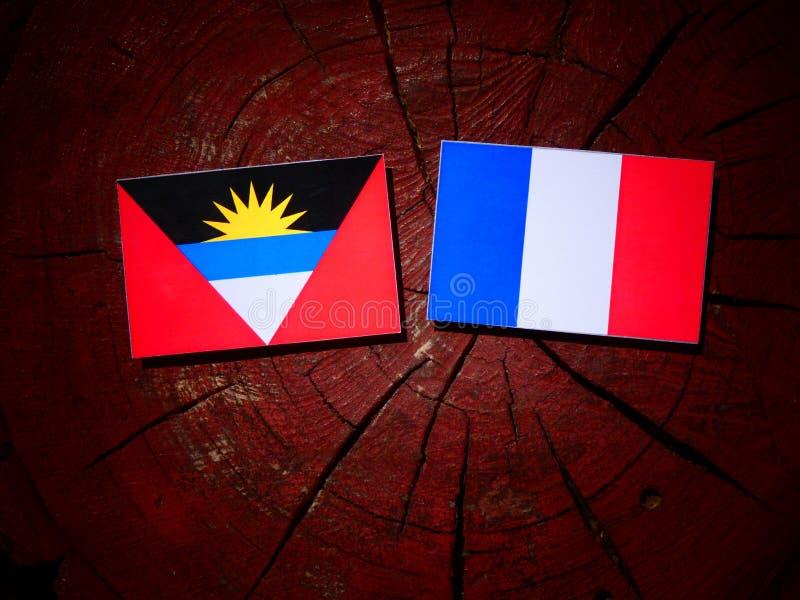 Drapeau de l'Antigua-et-Barbuda avec le drapeau français sur un isolat de tronçon d'arbre images libres de droits
