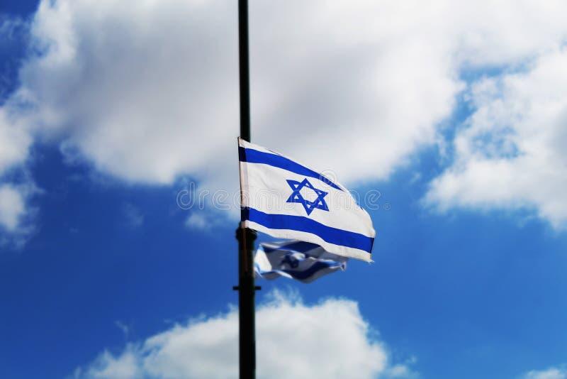 Drapeau de l'Israël accroché en l'honneur du Jour de la Déclaration d'Indépendance de l'Israël contre le ciel bleu photo libre de droits