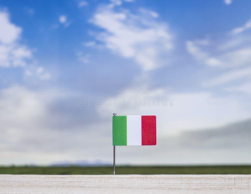 Drapeau de l'Italie avec le vaste pré et le ciel bleu derrière lui photographie stock