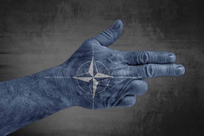 Drapeau de l'OTAN peint sur la main masculine comme une arme à feu photos stock