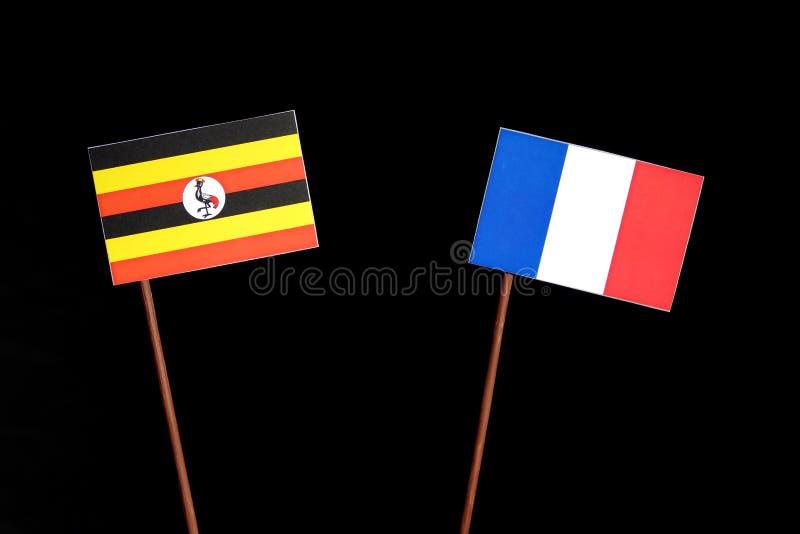 Drapeau de l'Ouganda avec le drapeau français d'isolement sur le noir photo stock