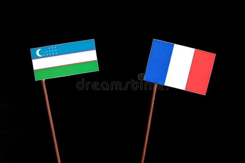 Drapeau de l'Ouzbékistan avec le drapeau français sur le noir images stock