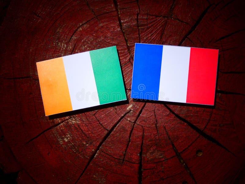 Drapeau de la Côte d'Ivoire avec le drapeau français sur un tronçon d'arbre d'isolement photo stock