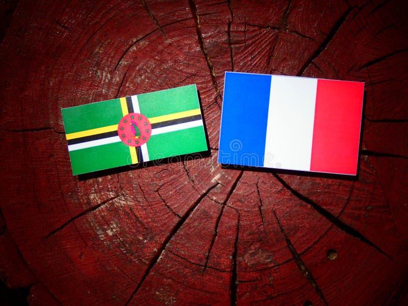 Drapeau de la Dominique avec le drapeau français sur un tronçon d'arbre d'isolement photos stock