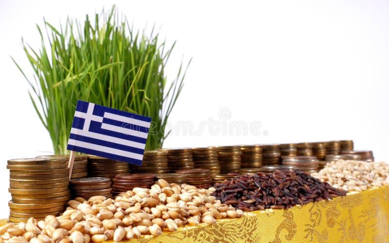 Drapeau de la Grèce ondulant avec la pile de pièces de monnaie d'argent et les piles du blé image libre de droits