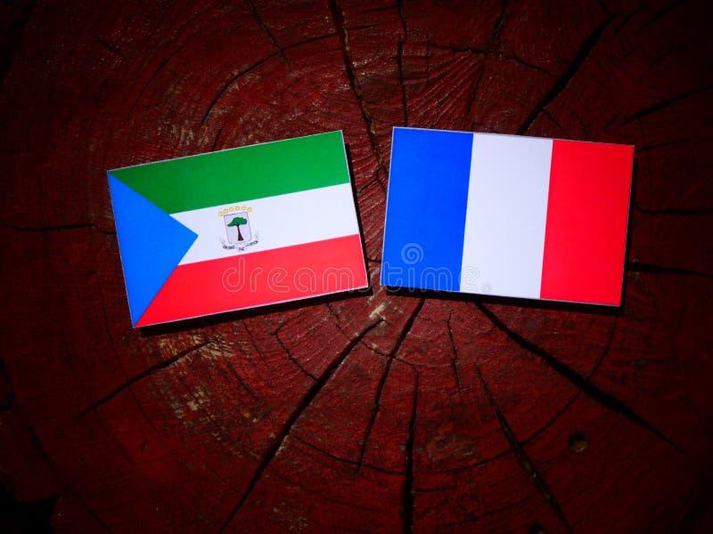 Drapeau de la Guinée équatoriale avec le drapeau français sur un tronçon d'arbre d'isolement photo libre de droits