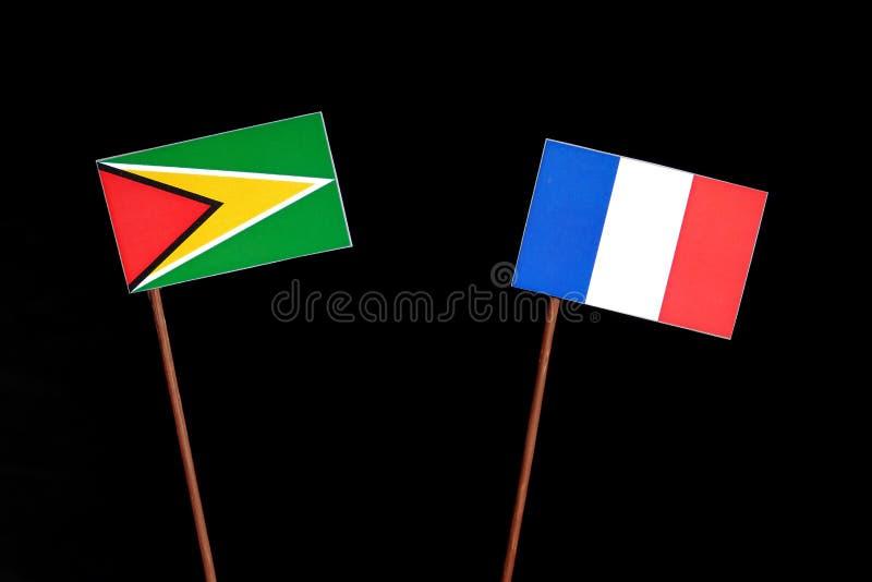 Drapeau de la Guyane avec le drapeau français d'isolement sur le noir photo stock
