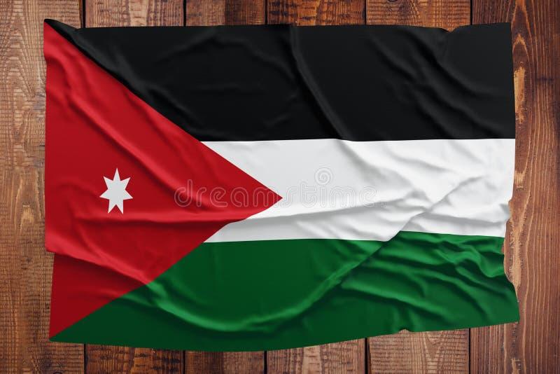 Drapeau de la Jordanie sur un fond en bois de table Vue sup?rieure froiss?e de drapeau jordanien photos stock