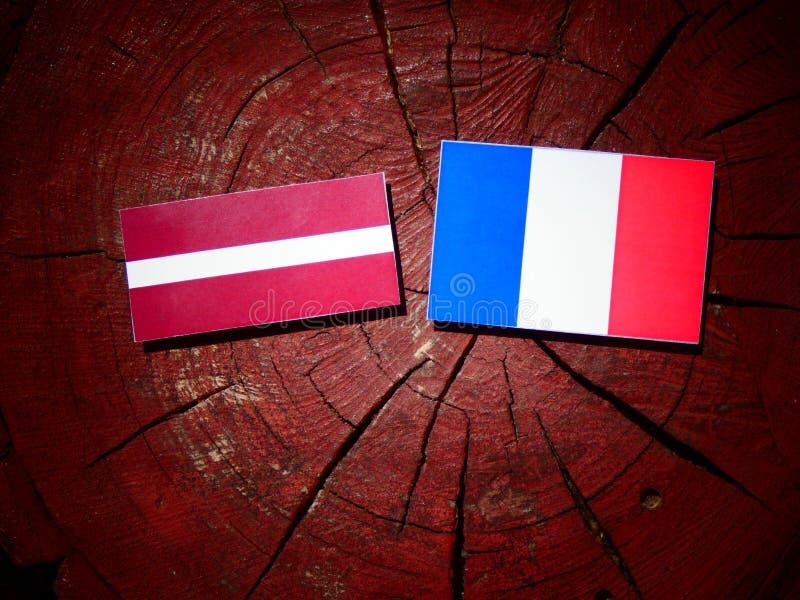 Drapeau de la Lettonie avec le drapeau français sur un tronçon d'arbre d'isolement photos libres de droits