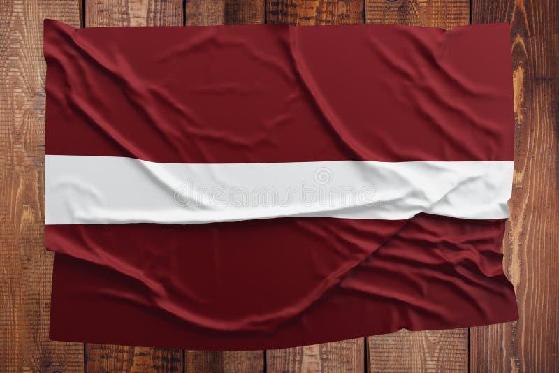 Drapeau de la Lettonie sur un fond en bois de table Vue supérieure froissée de drapeau letton photos stock