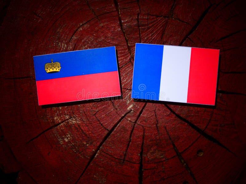 Drapeau de la Liechtenstein avec le drapeau français sur un tronçon d'arbre d'isolement image libre de droits