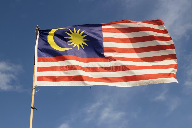 Drapeau de la Malaisie également connu sous le nom de vague de Jalur Gemilang avec le ciel bleu images libres de droits