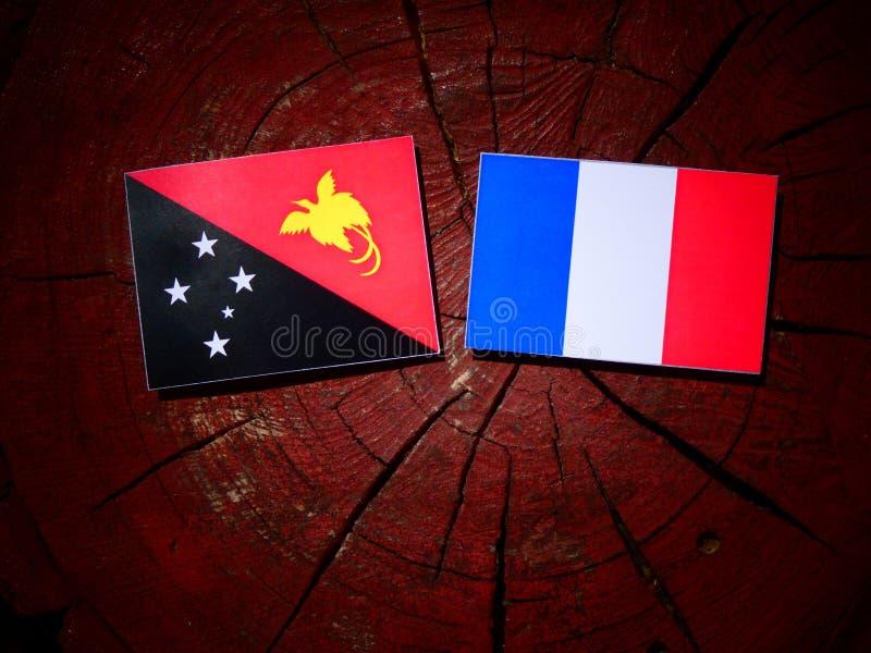 Drapeau de la Papouasie-Nouvelle-Guinée avec le drapeau français sur un tronçon d'arbre d'isolement image stock
