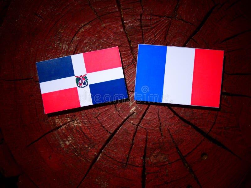 Drapeau de la République Dominicaine avec le drapeau français sur un isolat de tronçon d'arbre image stock