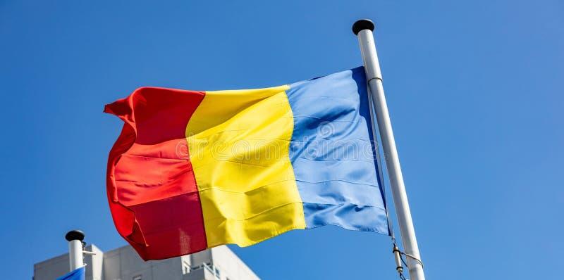 Drapeau de la Roumanie ondulant contre le ciel bleu clair photos libres de droits