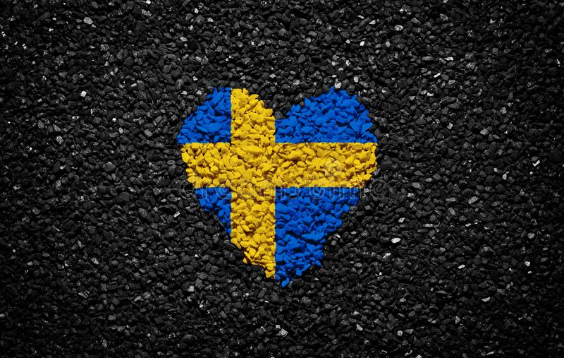 Drapeau de la Suède, drapeau suédois, coeur sur le fond noir, pierres, gravier et bardeau, papier peint texturisé images stock