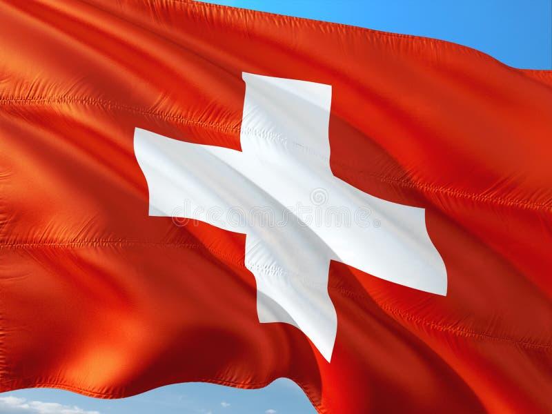 Drapeau de la Suisse ondulant dans le vent contre le ciel bleu profond Tissu de haute qualit? images stock