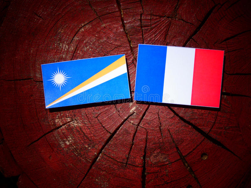 Drapeau de Marshall Islands avec le drapeau français sur un tronçon d'arbre d'isolement photographie stock