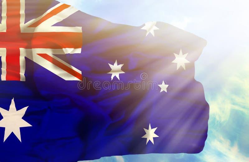 Drapeau de ondulation de l'Australie contre le ciel bleu avec des rayons de soleil images stock